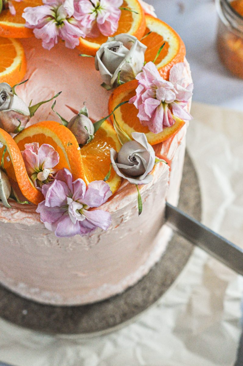 A close up shot of the top of a cake with oranges and flowers on it being sliced with a knife