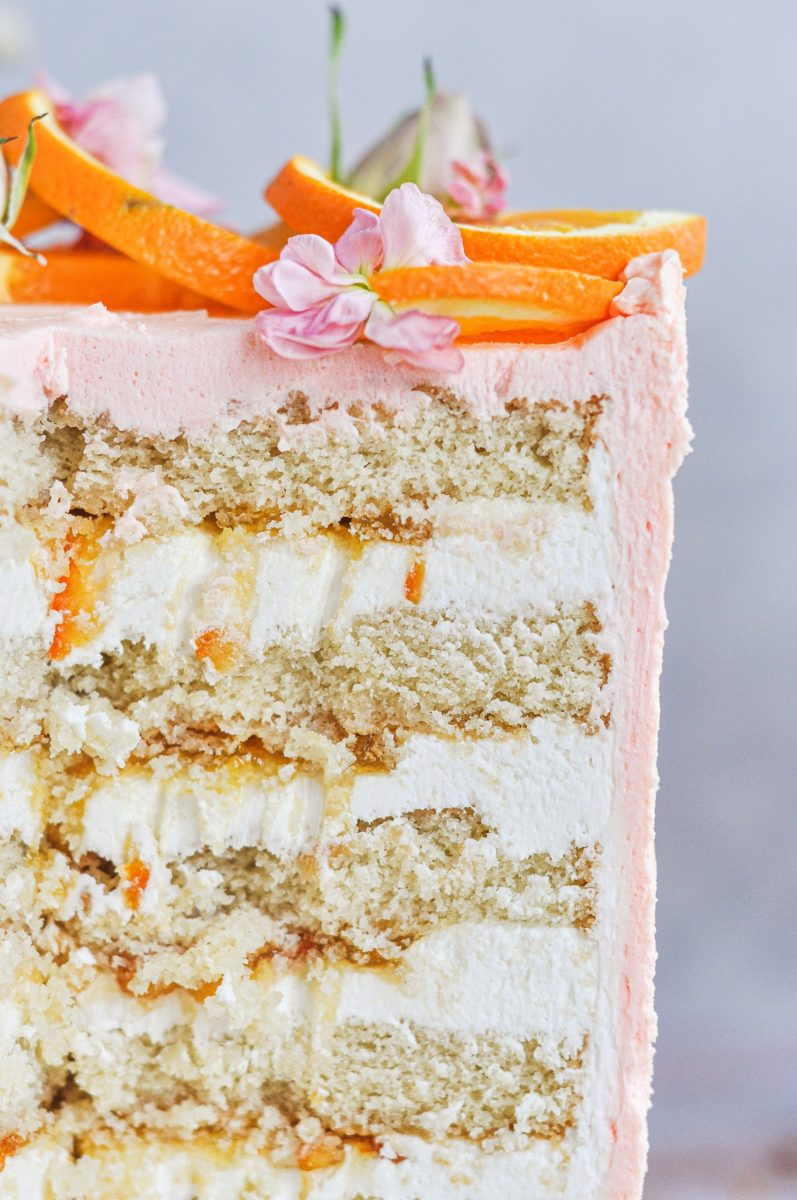 A close up shot of the inside of a cake with white frosting and orange filling