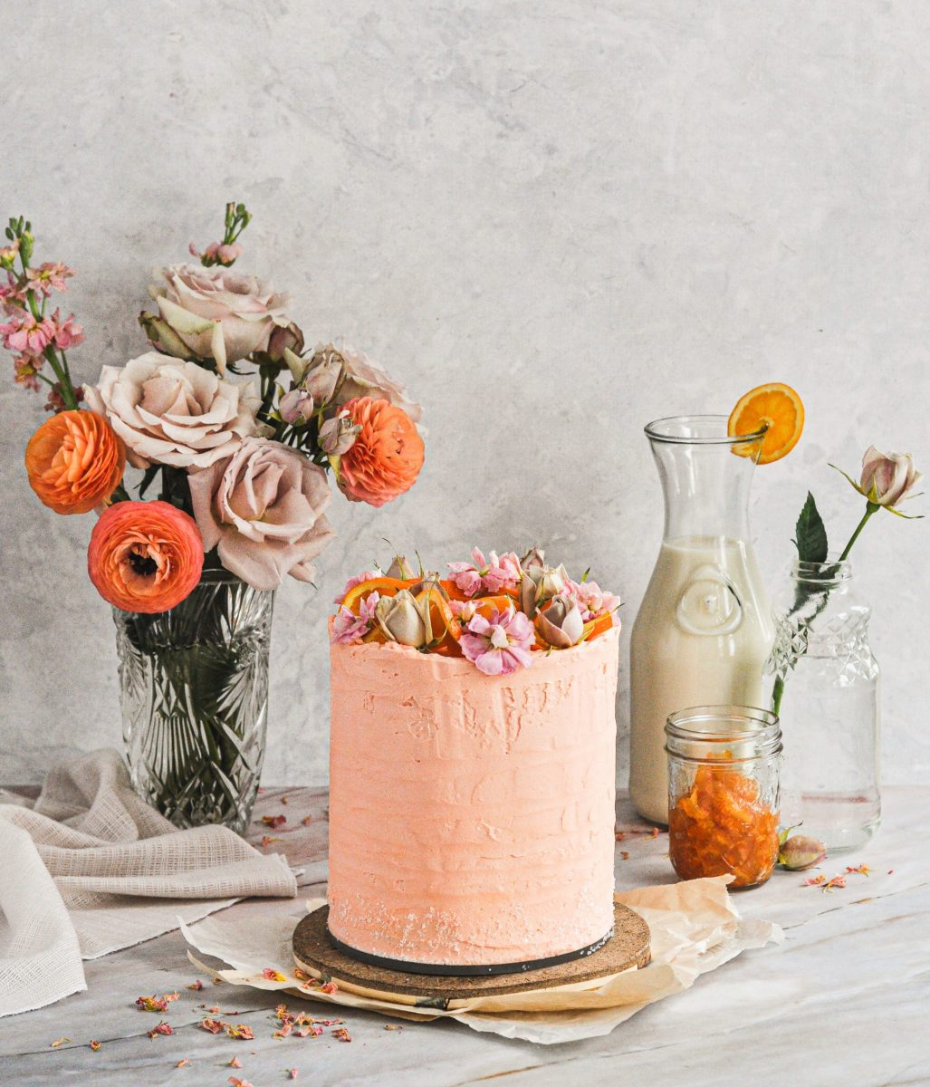 An orange cake topped with orange slices and fresh flowers sitting on a table with a flower vase and a milk craft.