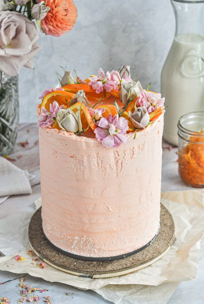 A light orange cake topped with orange slices and flowers.