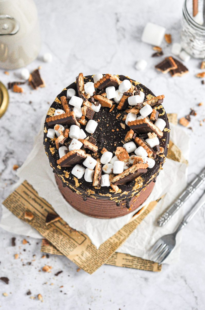 A cake top with chocolate covered cookies and mini marshmallows on it.