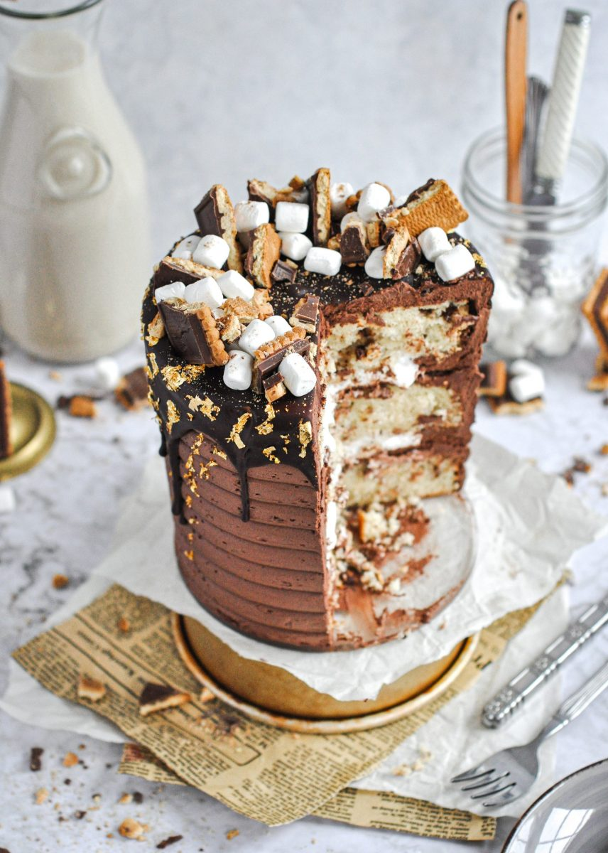 A s'mores cake topped with chocolate cookies, mini marshmallows, with dark chocolate frosting. There's a large slice taken out of it.