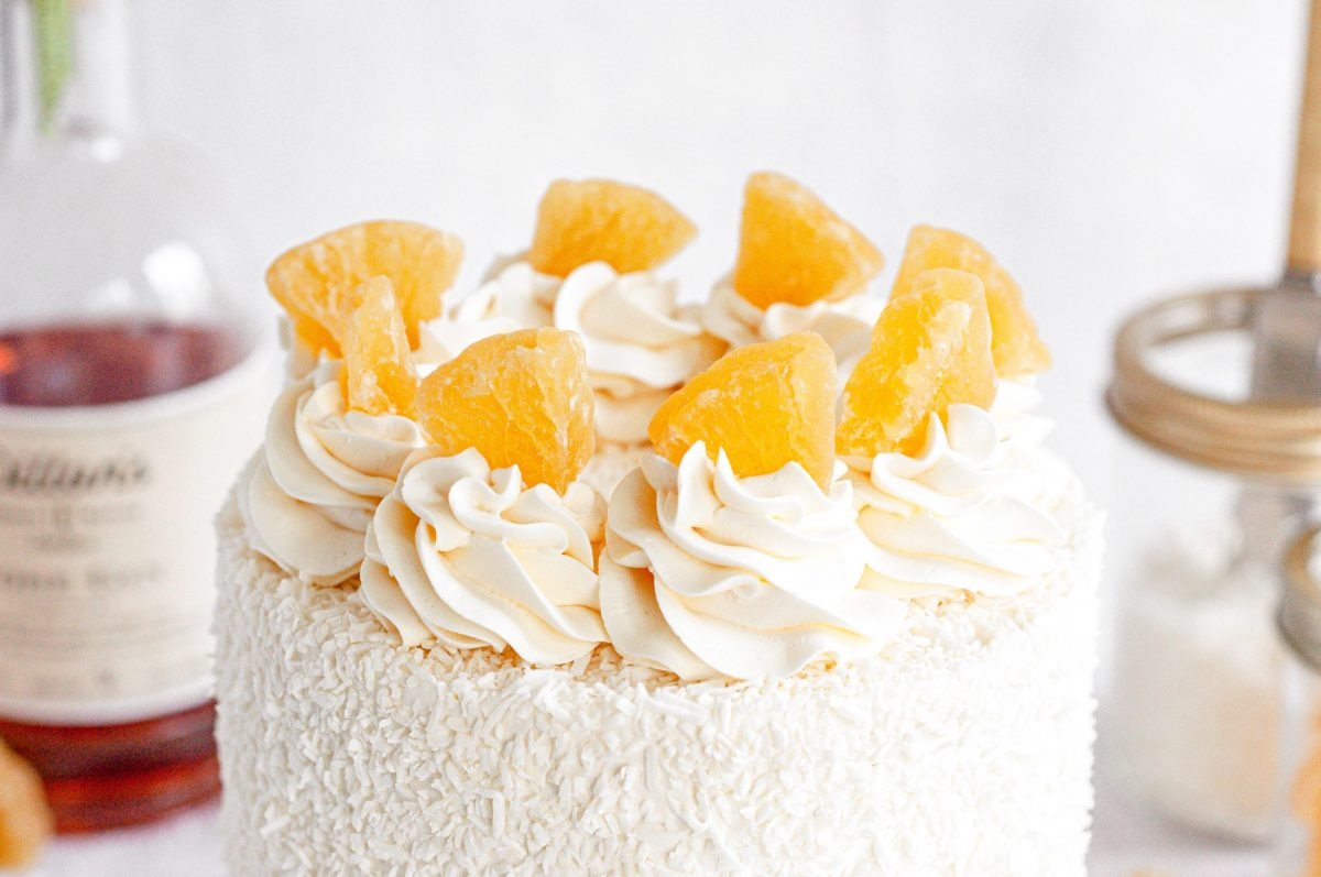A close up short of a cake top covered in shredded cocot and white frosting swirls with dried pineapples on top of each swirl.