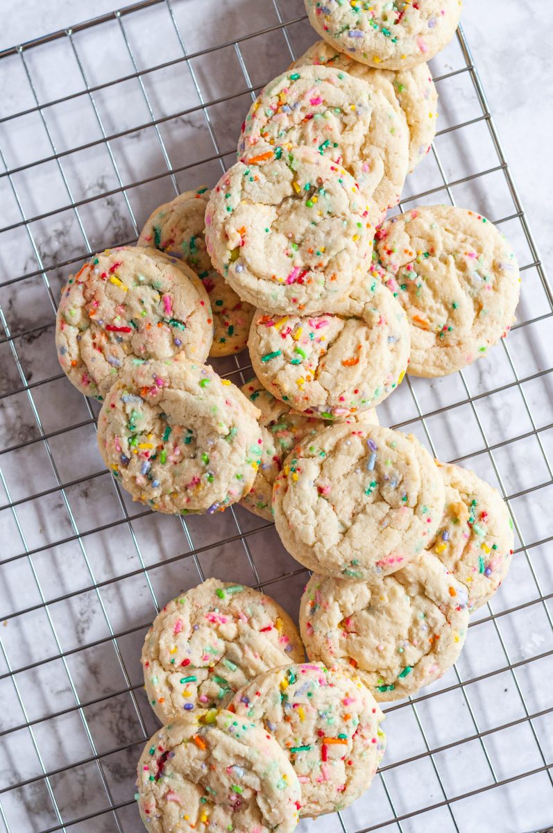Sprinkled sugar cookies all laying on a wire cooling rack.