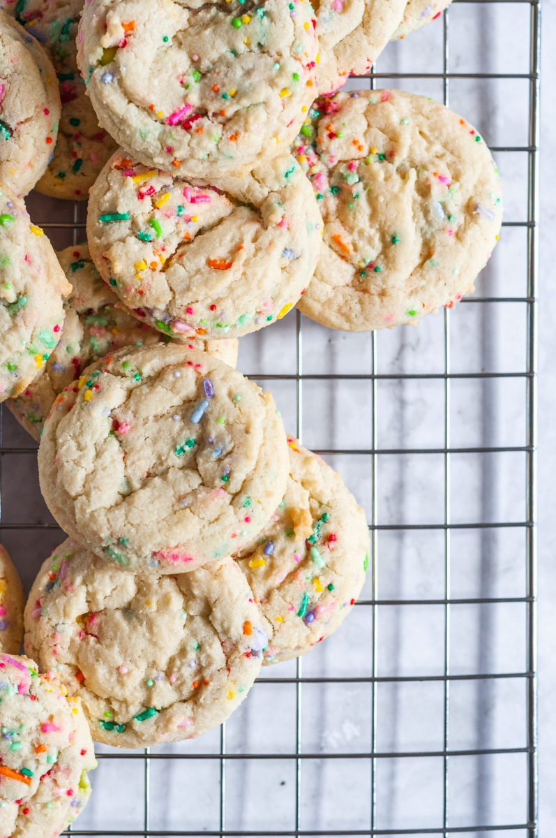 Fun sugar cookies full of brightly colored sprinkles sitting on a wire cooling rack.