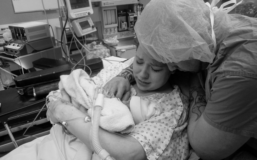 A black and white picture of a mother and father holding their premature baby.