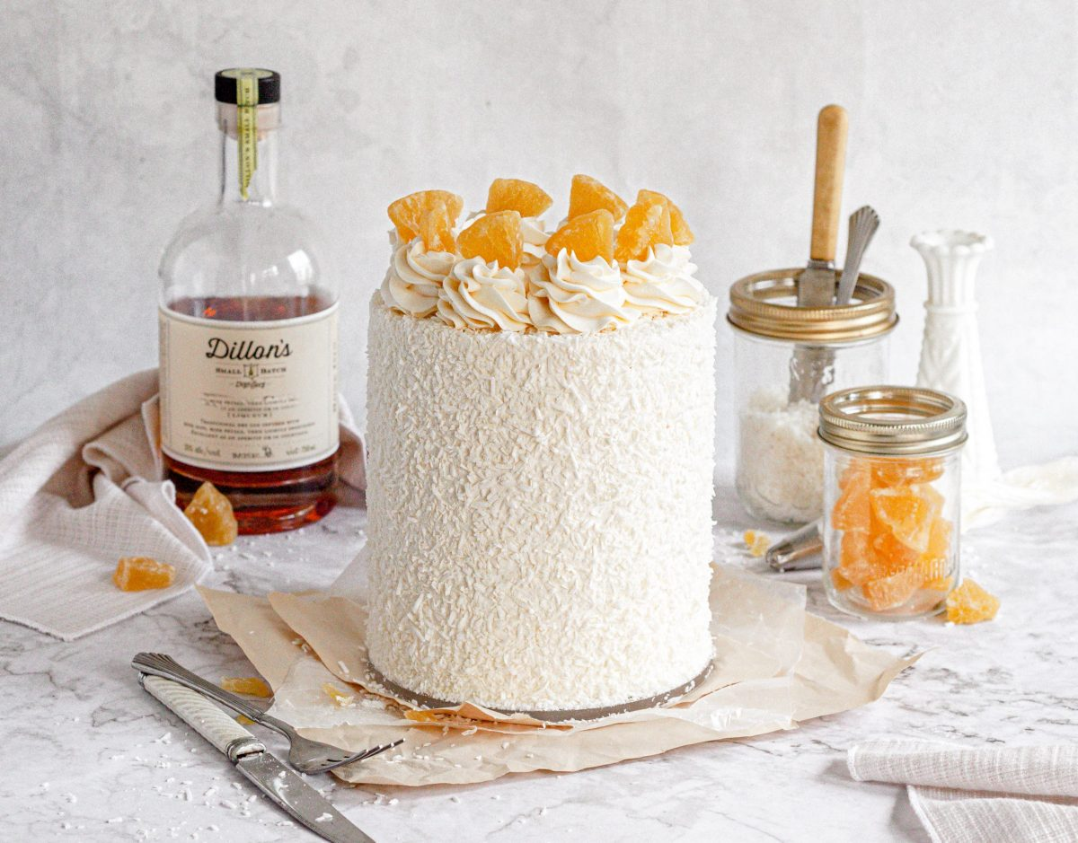 A pina colada cake covered in shredded coconut and topped with white frosting swirls and dried candied pineapples.