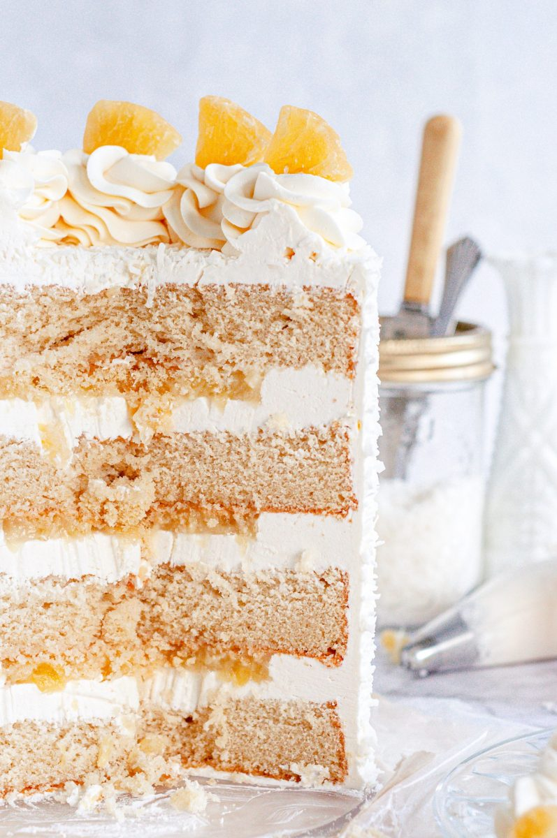 The inside shot of a pina colada layer cake. There is white frosting between each cake layer and pineapple filling.