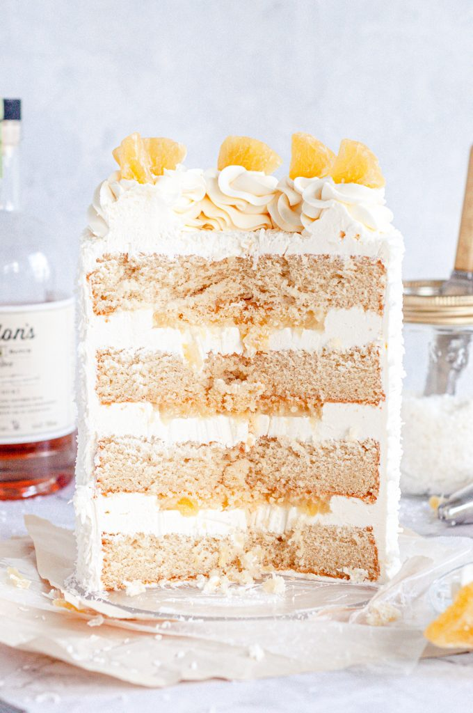 The inside of a pina colada cake that has white frosting between each cake layer and pineapple filling.