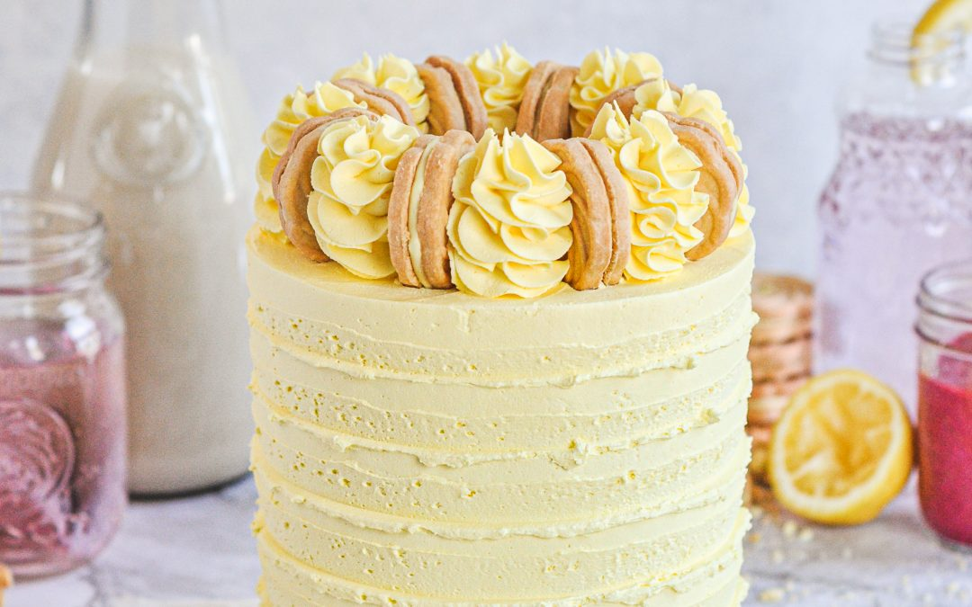A yellow frosted cake with fluffy buttercream swirls on top and a golden cookie between each swirl.