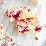 A close up picture of two white chocolate raspberry blondies stacked on each other.