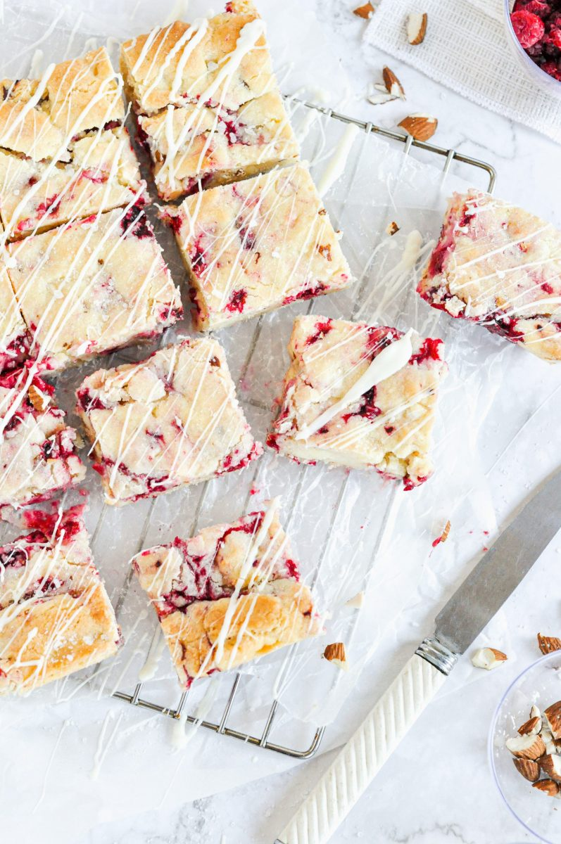 An overhead picture of white chocolate and raspberry blondies on a metal cooling rack.