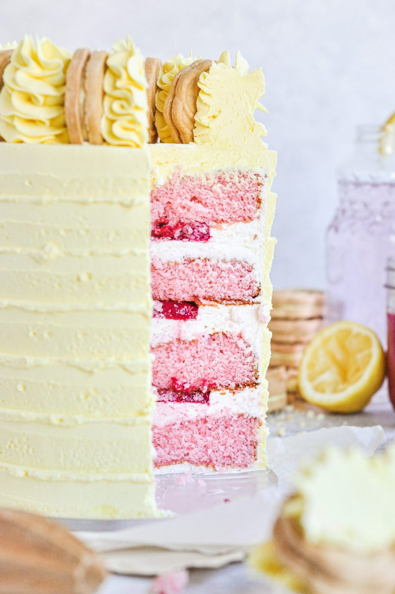 A yellow cake with a slice taken out of it. You can see the inside cake layers which are pink and have a bright pink raspberry filling in between each layer.