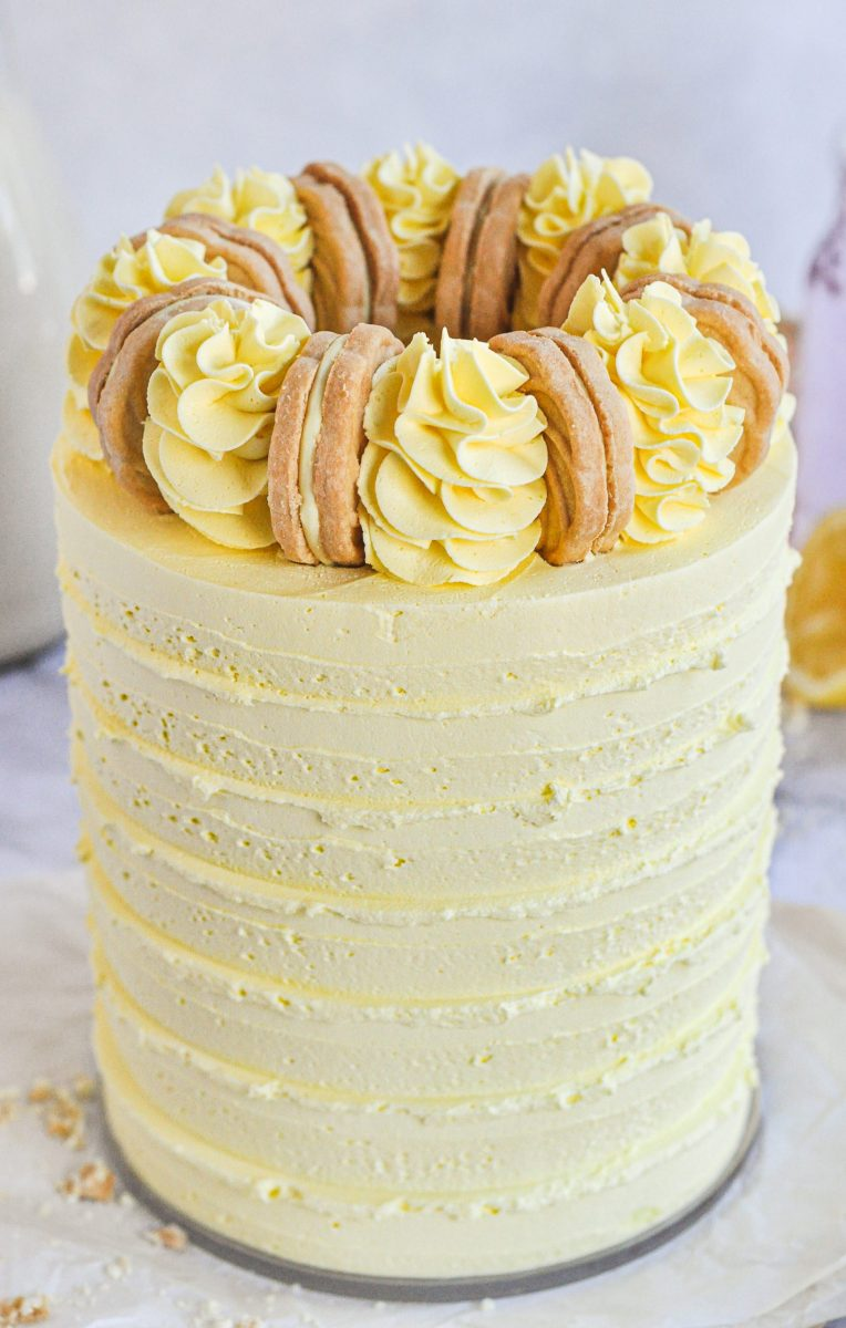 A yellow cake with yellow frosting swirls on top and a golden cookie between each swirl.