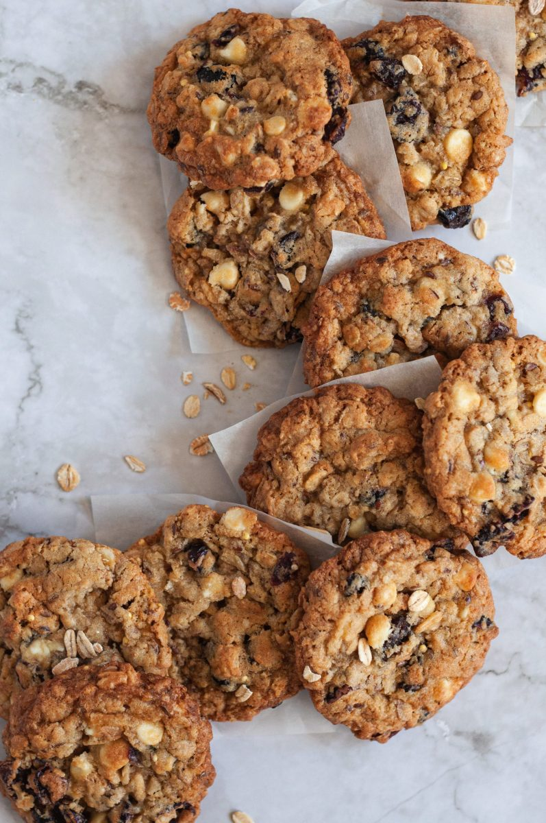 A handful of golden brownoatmeal cookies laying on parchment squares with whole grain oats.