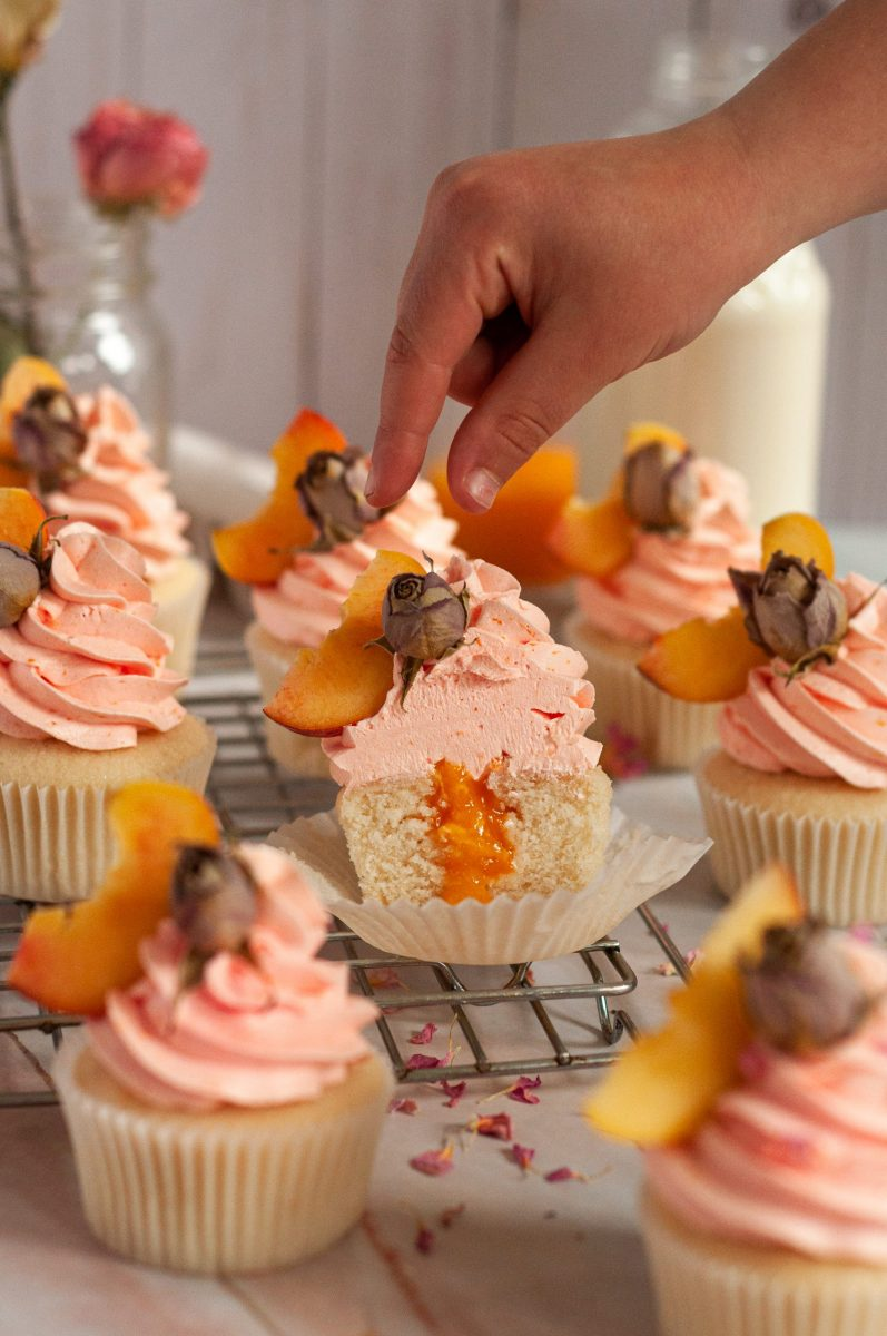 Peach rose flavored cupcakes sitting on a cooling tray topped with a light orange frosting swirl and a slice of fresh peach and dried rose for decor on top of each swirl. The center cupcake is cut in half and the peach filling is spilling out of the center. There is a hand coming in the frame reaching for the peach slice on top.