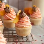 Peach rose flavored cupcakes with a peachy orange frosting swirl and a slice of fresh peach and dried rose on top for decor.