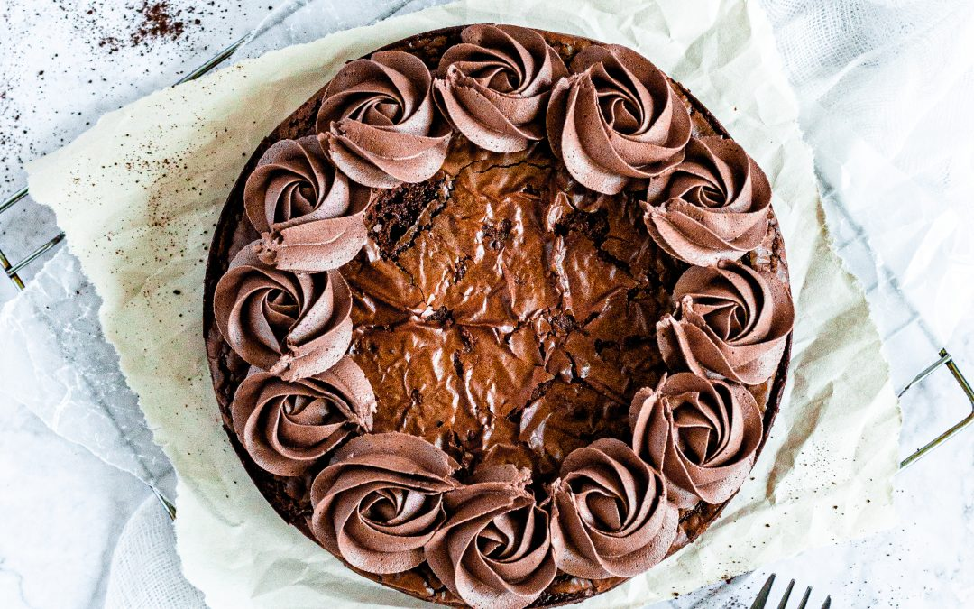A circular brownie with a chocolately crinkle top and coverede in chocolate fudge frosting swirls around the border.