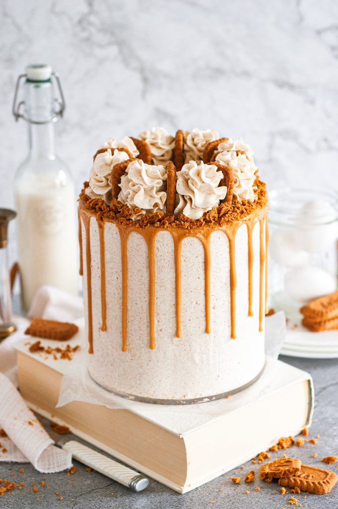 A white frosted biscoff cookie butter cake with a golden brown cookie butter drip. The top has frosting swirls around it and a biscoff cookie in between each swirl. The cake is sitting on a table with a milk jug and cookies in the background.