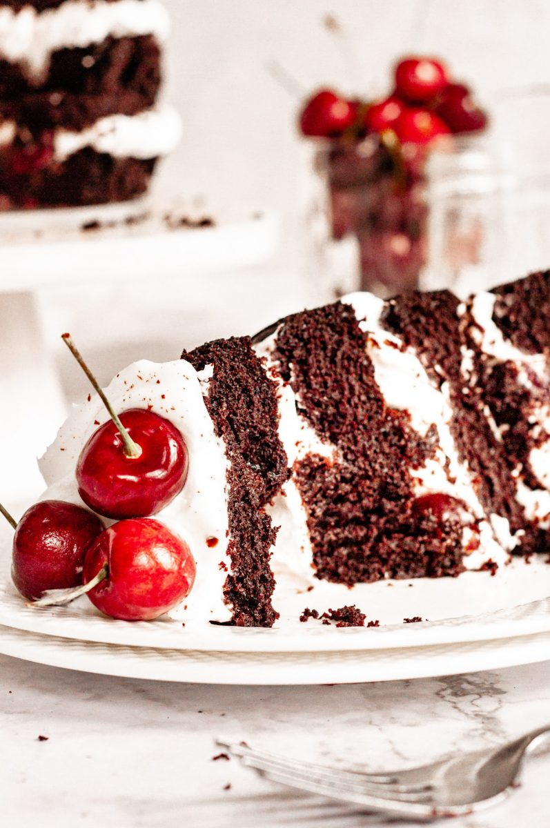A slice of black forest cake sitting on a white plate. There is a large bite taken out of it.