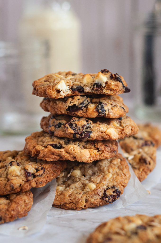 A messy short stack of oatmeal cookies on a piece of white parchment paper full of dried cherries and white chocolate chips.