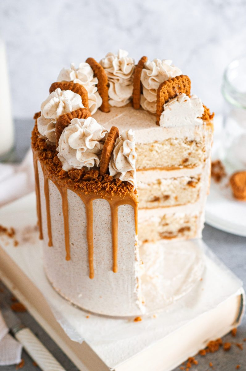 A white frosted cake coverfed in a golden brown cookie butter drip and topped with biscoff cookies between frosting swirls.