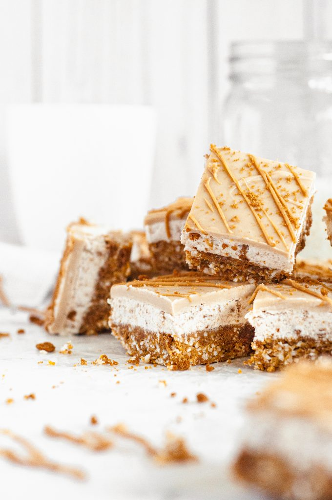A haphazard stack of light golden brown cookie butter bars with a drizzle of cookie butter on top.