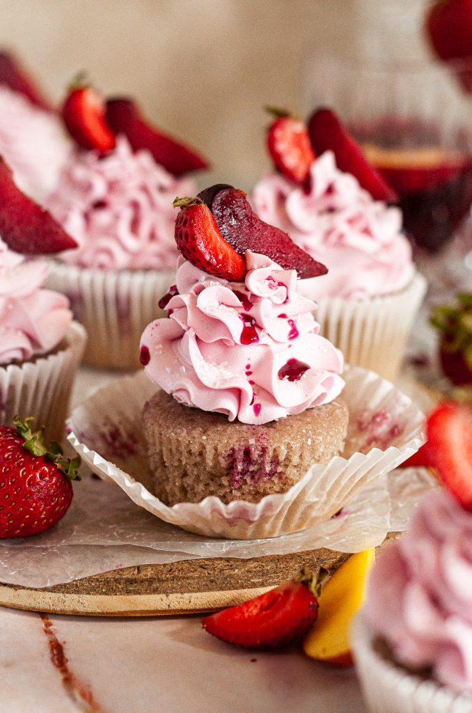 Sangria cupcakes topped with fluffy pink frosting swirls and fresh fruit on top. The cloest cupcake has the cupcake wrapper opened.