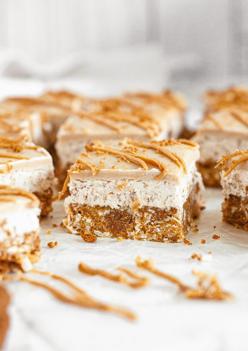 Light golden brown cookie butter bars sitting on a white table. They have three distinct layers and are covered in a golden brown cookie butter drizzle.