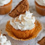 A pumpkin cupcake topped with fluffy white cream cheese frosting on top and half a gingersnap cookie.