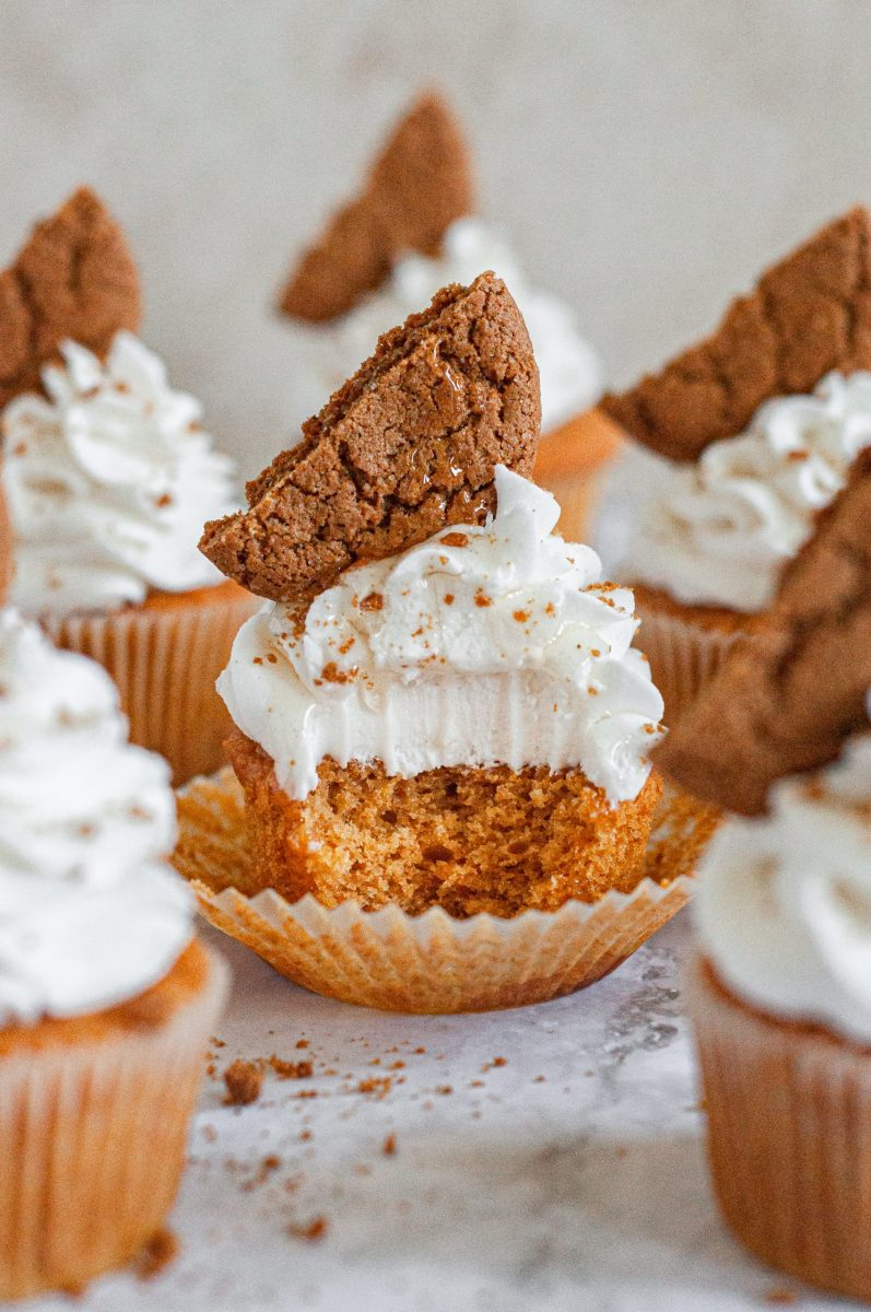 A pumpkin cupcake topped with fluffy white cream cheese frosting on top and half a gingersnap cookie. A large bite is taken out of the cupcake.