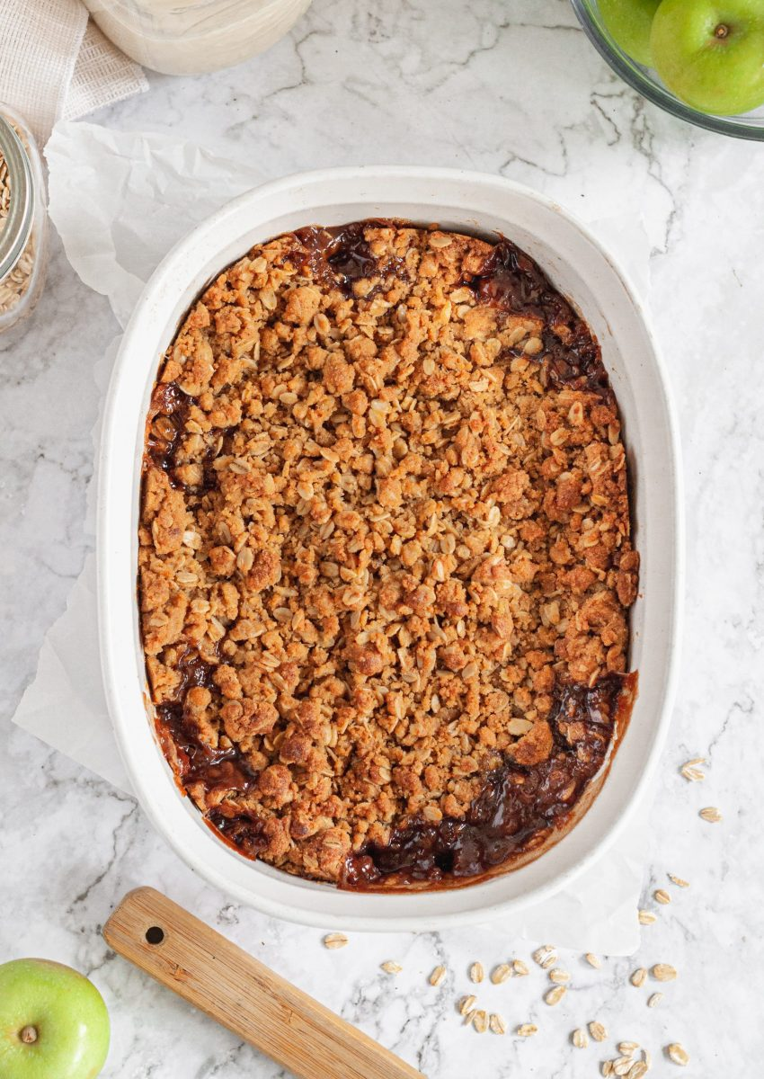 A top view of a golden brown baked apple crisp is an oval white baking dish sitting on a table next to green apples and oats.