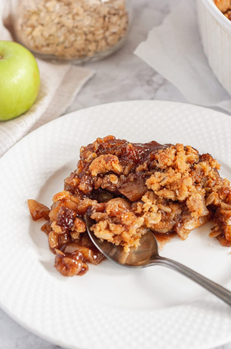A close up shot of a large scoop of baked golden brown apple crisp on a bright white plate with a spoon in it.