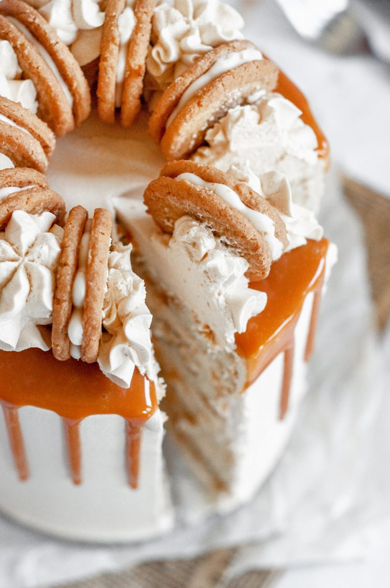 A close up picture of a salted caramel cake covered in white frosting and a golden amber caramel drip. There's a slice cut and it's being taken out of the cake.
