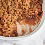A close-up shot of a golden brown carmalized apple crisp in a white baking dish with flecks of cinnamon in the bottom.