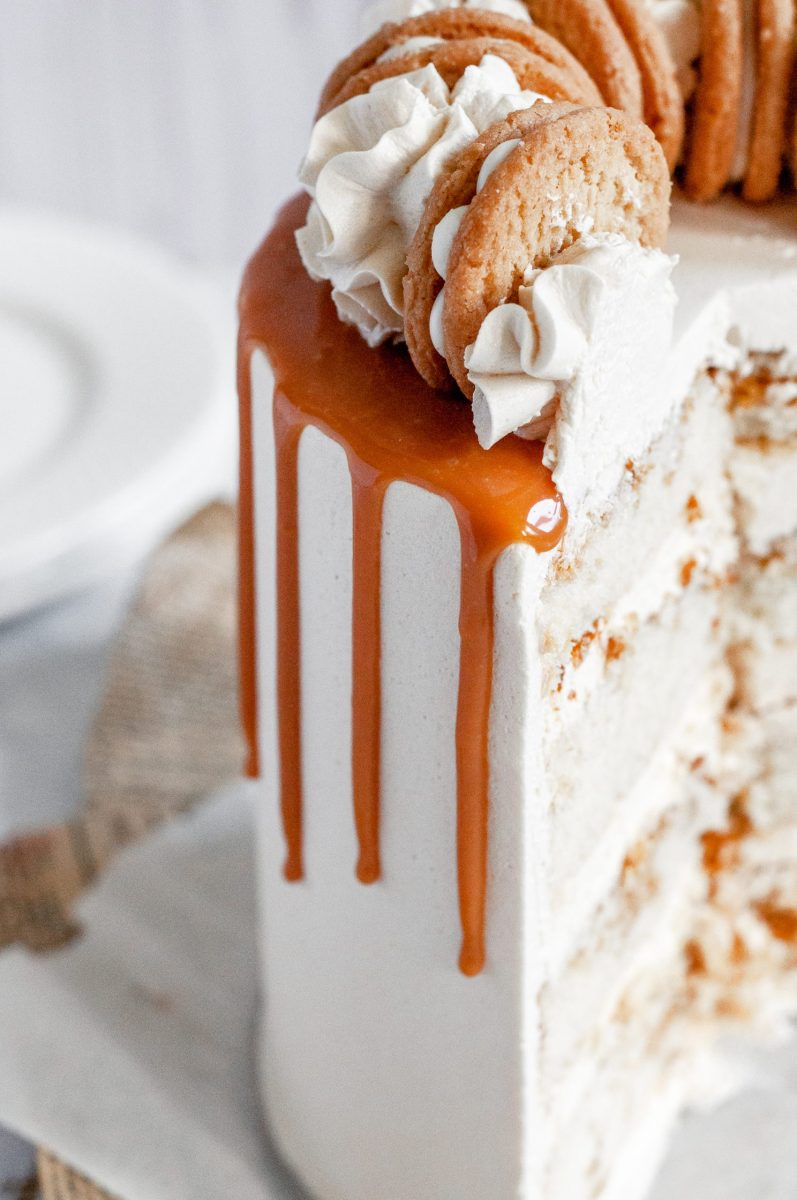 A close up picture of a white frosted cake with white buttercream swirls on top, a cookie between each swirl, and a caramel drip going down the sides.