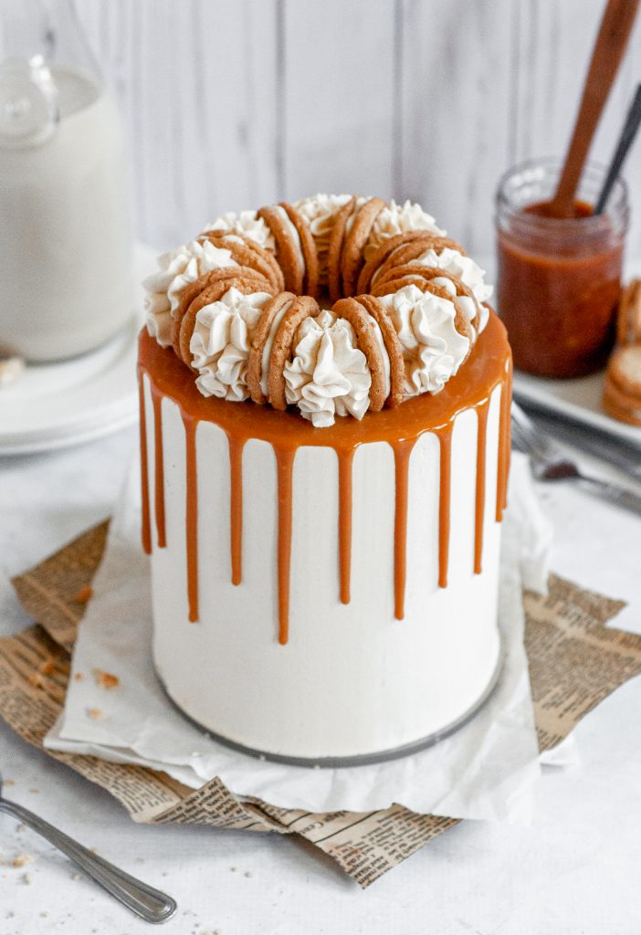 A salted caramel cake topped with white buttercream swirls and a cookie between each swirl. There is caramel sauce dripping over the edge all the way aound the cake.