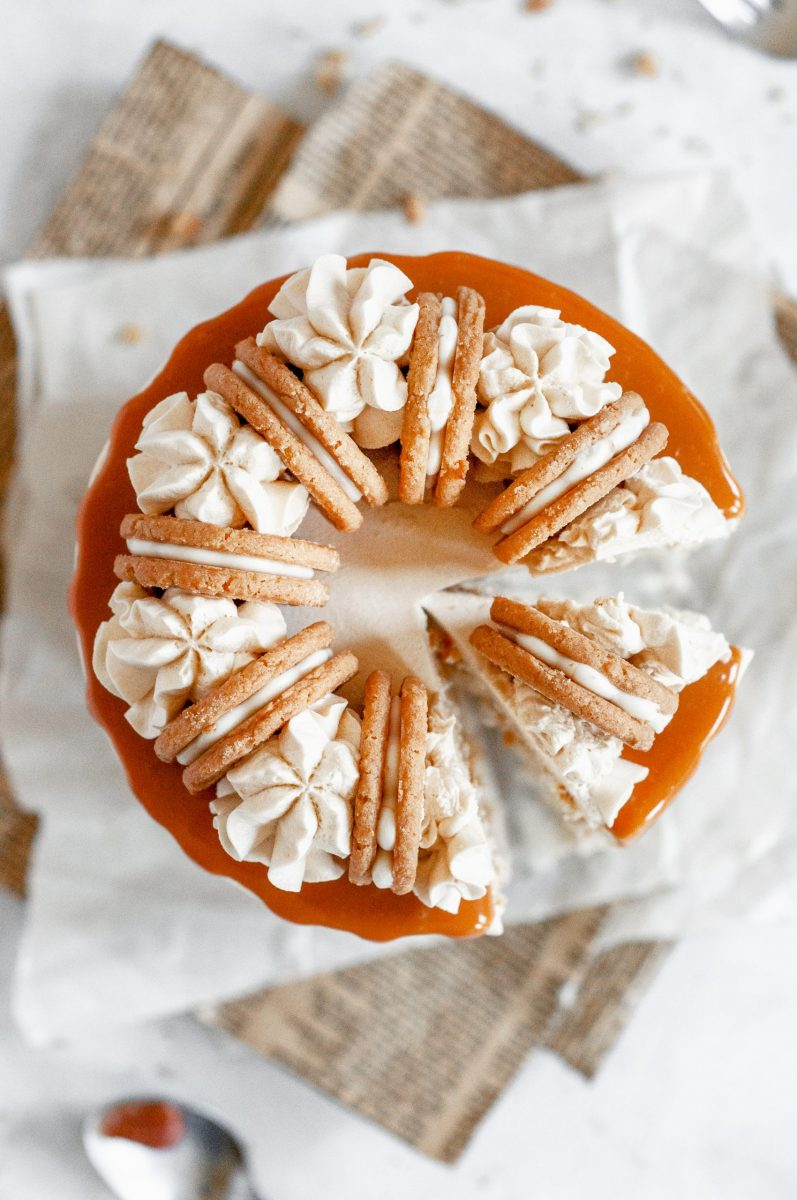 The top view of a salted caramel cake. The frosting is white and the top has frosting swirls around it with a cookie between each swirl. A slice is cut out of the cake.