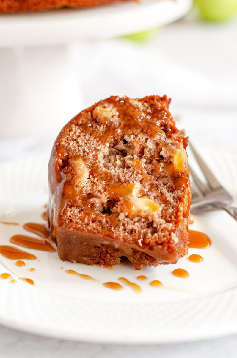 A close up picture of a slice of golden brown apple bundt cake loaded with apple chunks. It's sitting on a white plate with a silver fork beside it and drizzled with toffee sauce.