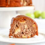 A slice of apple bundt cake covered in toffee sauce is sitting on a wehite plate on the table infront of the bundt cake that is on a cake stand in the background.