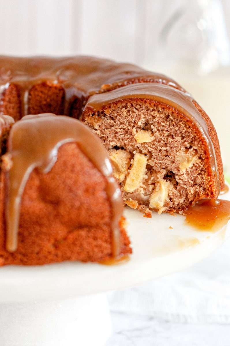 An apple bundt cake covered in toffee sauce with a large slice taken out of it. You can see inside the bundt cake and it's full of apples.