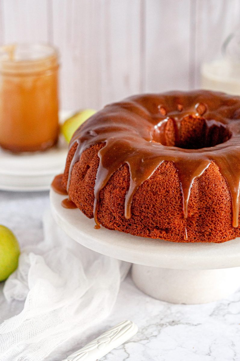 An apple bundt cake with toffee sauce dripping all over it.